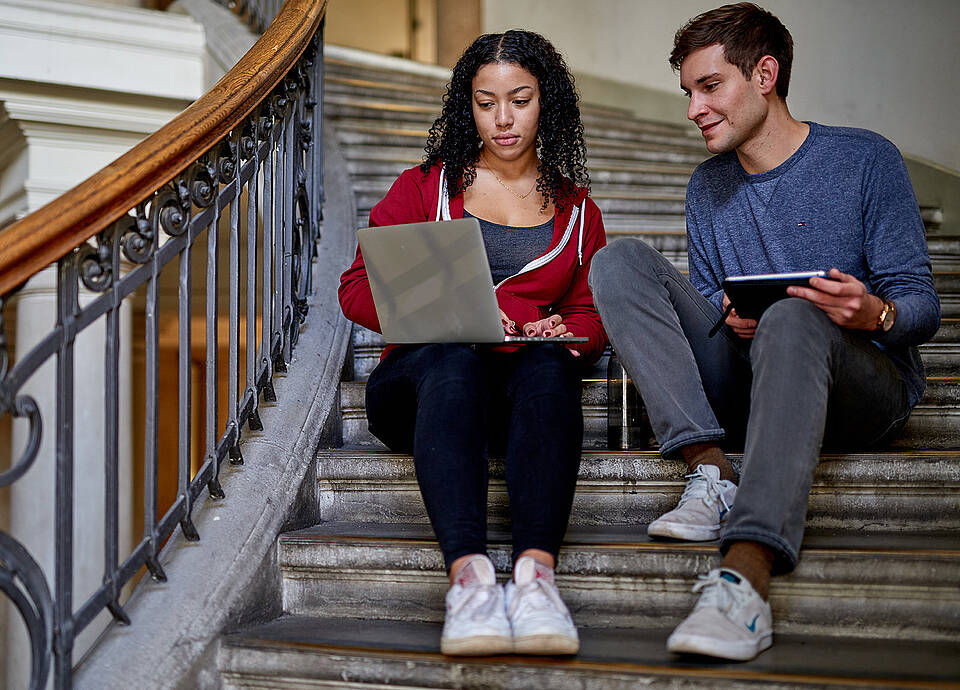Students sitting on stairs, working with a computer