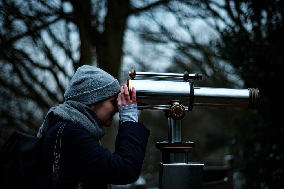 A person looking through a telescope