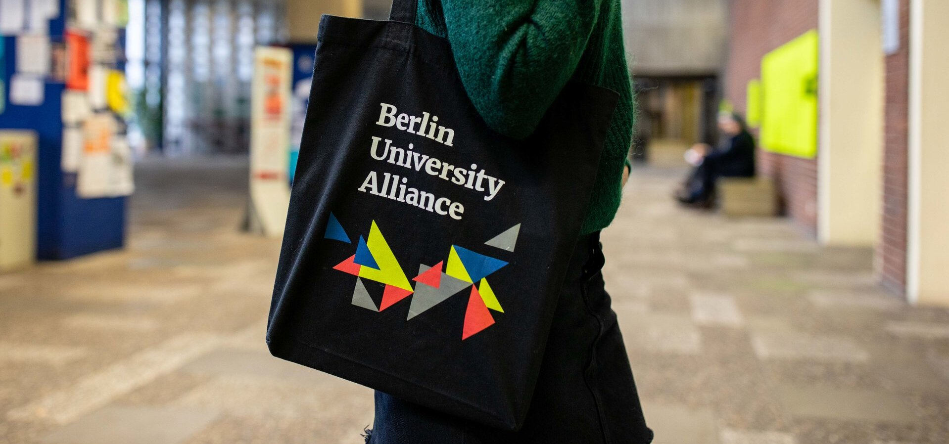 Person mit dem Beutel der Berlin University Alliance